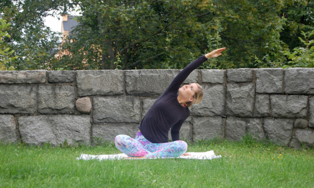 SIDESTREKK: Sett deg med benene i kryss, løft armen over hodet, og strekk deg sidelengs og oppover. Hold rumpen på bakken, og strekk rygg og mage. Bytt deretter arm, og hold posisjonen i minst ti åndedrag. FOTO: Johanna Bengtsson