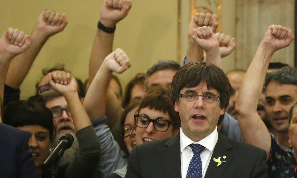 SYNGER KATALANSK HYMNE: Catalonias president Carles Puigdemont risikerer opptil 30 års fengsel for opprør etter dagens vedtak om løsrivelse. Her synger han den katalanske hymnen etter avstemningen i parlamentet i dag. Foto: NTB Scanpix/AP/Manu Fernandez