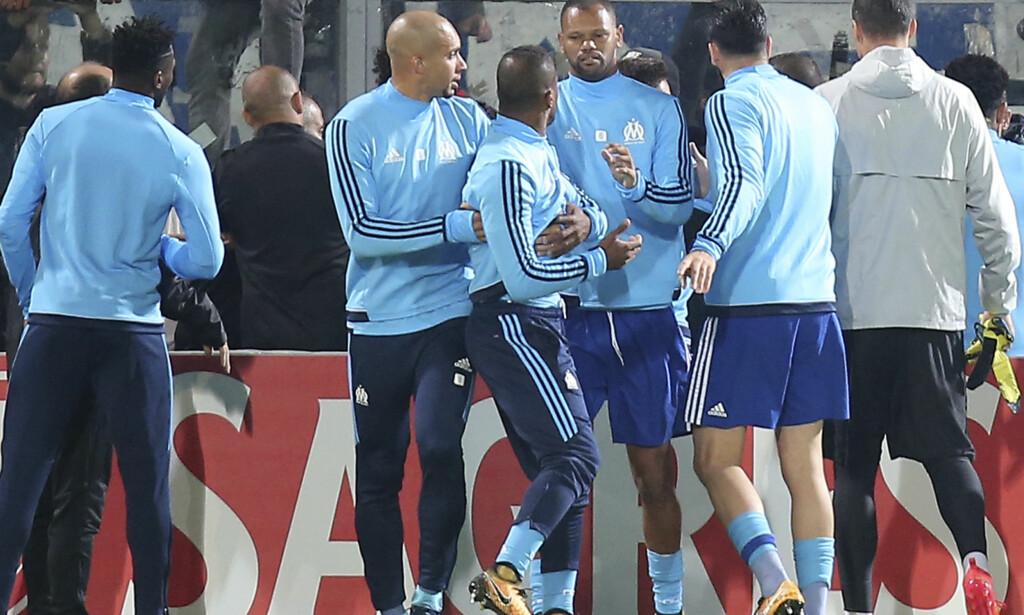 UTVIST: Patrice Evra trekkes bort fra situasjonen av sine lagkamerater etter å ha fått rødt kort før avspark i europaligakampen mot Vitória Guimarães. Han sparket etter en tilskuer. Foto: Luis Vieira, AP / NTB scanpix
