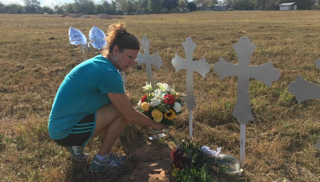 TUNGE TIDER: Cindy Wyatt legger ned blomster ved korsene som er plassert på et jorde i Sutherland Springs for å minnes de 26 drepte. Foto: Vegard Kristiansen Kvaale / Dagbladet