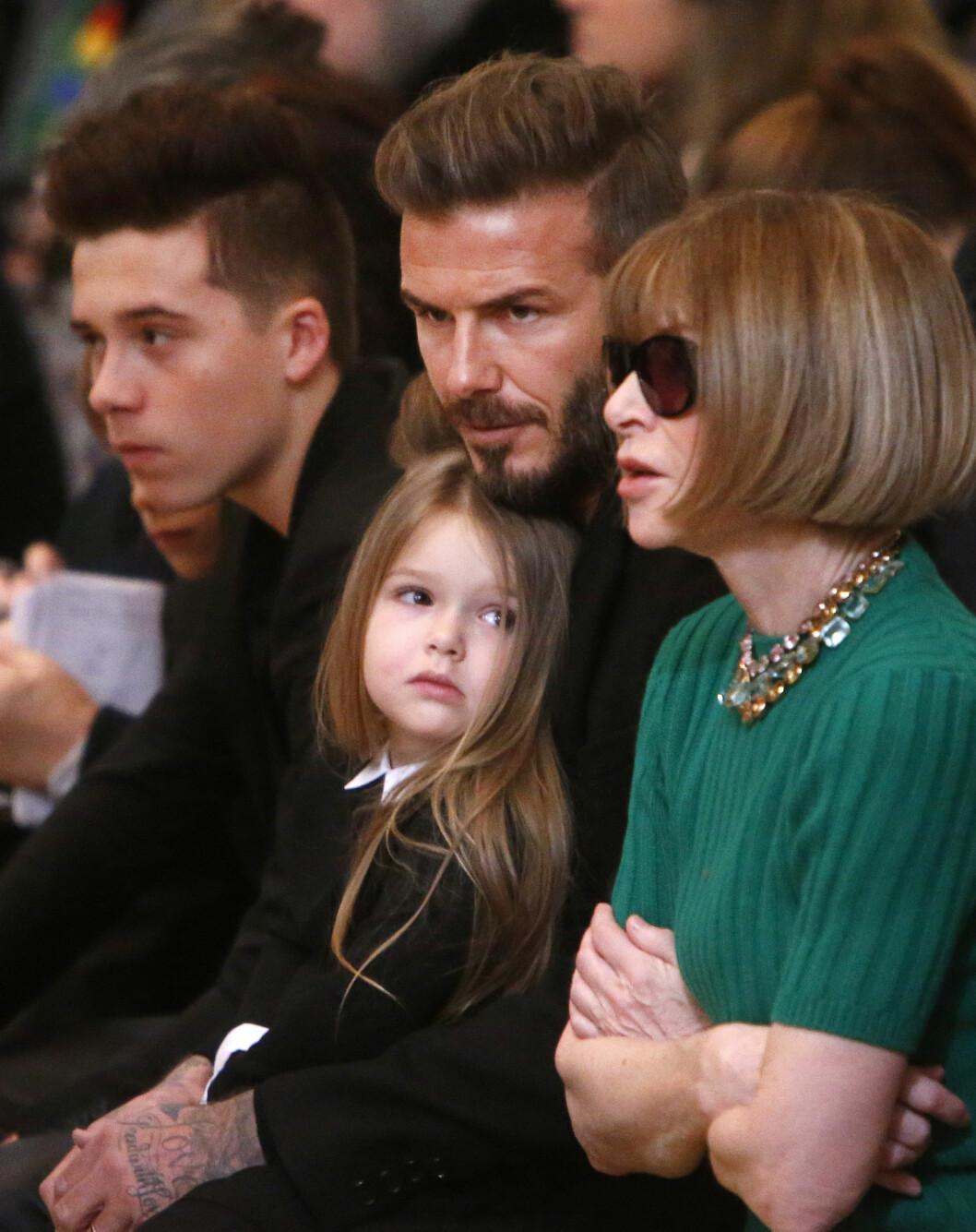 PÅ PAPPAS FANG: Harper Beckhem sitter trygt på pappas fang under New York Fashion Week. Harper lar seg fascinere av Vogue-redaktør Anna Wintour. Foto: NTB Scanpix