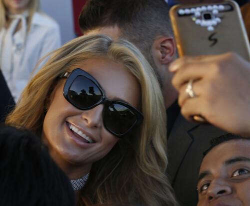 <strong>SELFIEDRONNING:</strong> Paris Hilton oppfant kanskje ikke konseptet selfie, men har gjennom karrieren sin tatt enormt mange bilder av seg selv. Her stiller hun opp på et bilde med en fan tidligere i november i Mexico. Foto: AP Photo, NTB scanpix