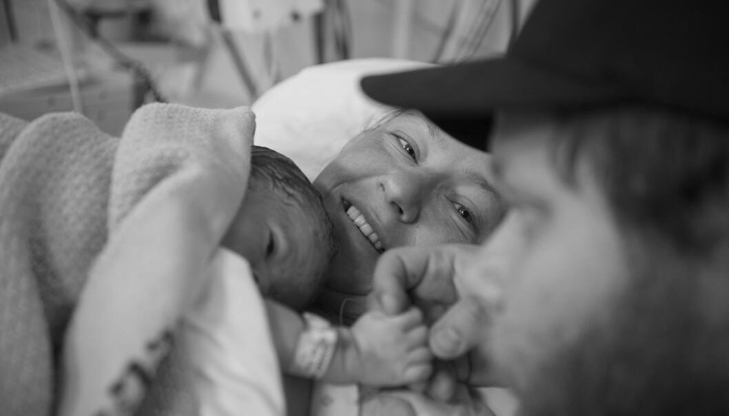 PAPPAS HÅND: Helt fersk, men med ro i blikket og kraft i fingrene, møter Loke mammaen og pappaen sin. Ved siden av sto fødselsfotograf Eva Rose og dokumenterte det hele til boken Fødsel, skrevet av Trine Dahlman. Foto: Eva Rose