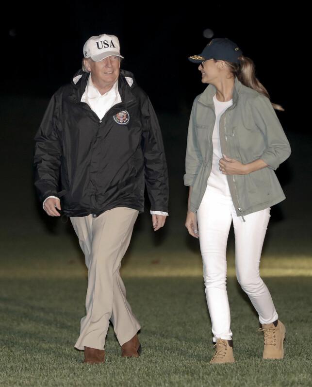 NED PÅ JORDA?: Selv om mange har stilt seg kritisk til Melania Trumps antrekk gjennom året, mener andre at det har bedret seg denne høsten. Her er hun fotografert i Puerto Rico i oktober i et nokså jordnært antrekk bestående av boots, jeans og caps. Donald har gått for samme stil. Foto: NTB scanpix