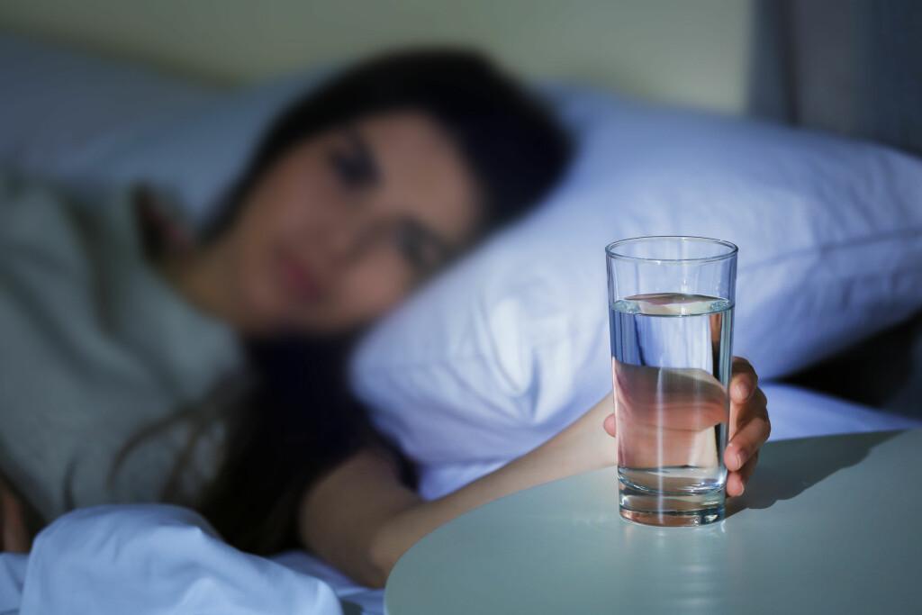 PLAGET MED MUNNTØRRHET? Det kan være lurt å ha et glass vann stående på nattbordet. Ved munntørrhet på natten bør man la vannet skylle godt rundt i munnen før det svelges slik at munnen holdes fuktig lengst mulig. Foto: Shutterstock