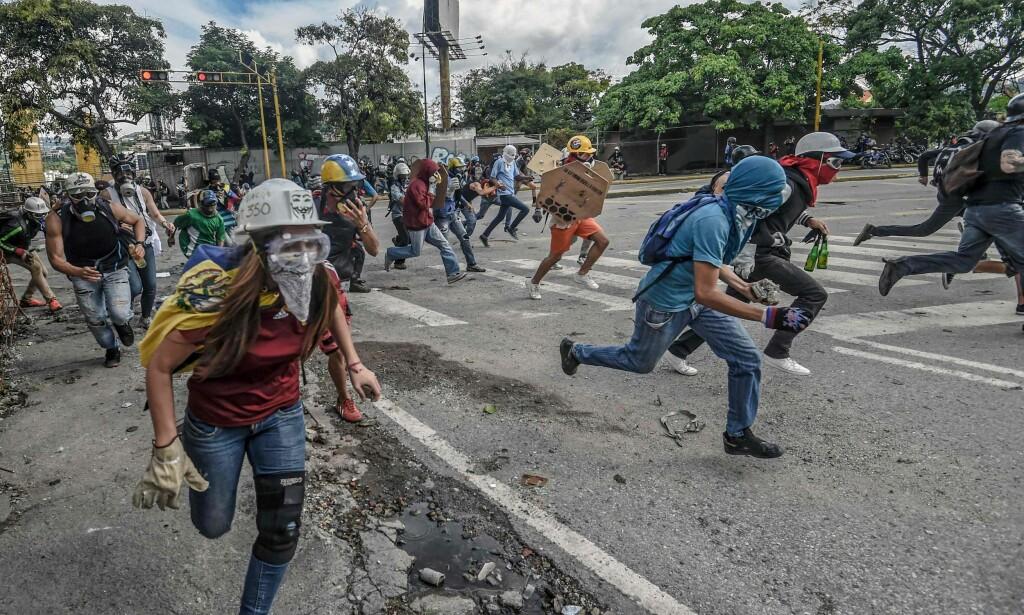 KRISE: Aktivister gjør opprør i gatene i Venezuelas hovedstad Caracas i forkant av valget i juli. Venezuela er i en dyp økonomisk krise og regjeringen og opposisjonen er fortida på Den dominikanske republikk for å forhandle om hvordan de skal løse krisa. Foto: AFP / NTB scanpix