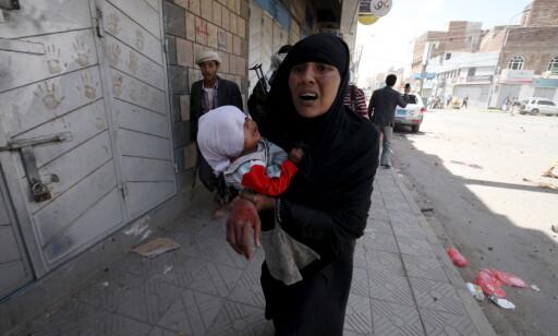 SIVILE TAP: En skadd kvinne bærer et lite barn etter et flyangrep like ved eks-president Ali Abdullah Saleh i mai 2015. Saleh overlevde en rekke drapsforsøk, men i går ble han drept, 75 år gammel. Foto: Mohamed al-Sayaghi   / Reuters / Scanpix