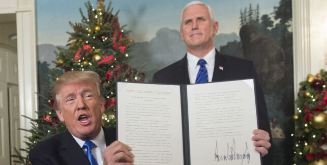 """US President Donald Trump holds up a signed memorandum after he delivered a statement on Jerusalem from the Diplomatic Reception Room of the White House in Washington, DC on December 6, 2017. President Donald Trump on Wednesday recognized the disputed city of Jerusalem as Israel's capital -- a historic decision that overturns decades of US policy and risks triggering a fresh spasm of violence in the Middle East.""""I have determined that it is time to officially recognize Jerusalem as the capital of Israel,"""" Trump said from the White House.""""It's the right thing to do."""" / AFP PHOTO / SAUL LOEB"""