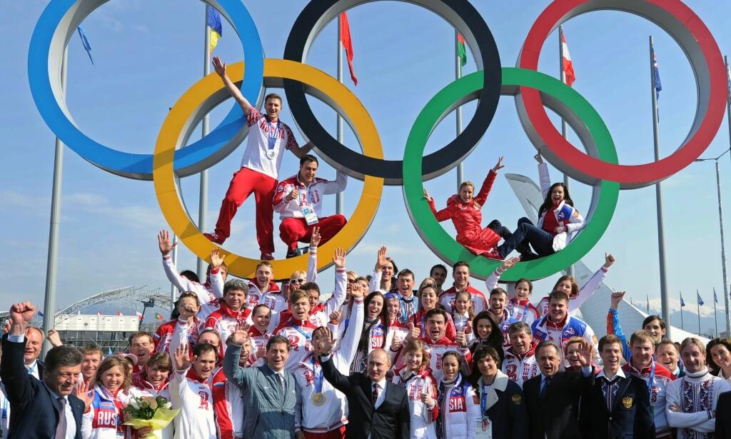 UTESTENGT: Enkelte russiske utøvere kan få mulighet til å delta i OL, om de kan bevise for et panel utvalgt av blant annet IOC og WADA om deres uskyld. Her poserer flere av utøverne i Sotsji sammen med Vladimir Putin og livstidsutestengte Vitalij Mutko. Foto: AFP PHOTO / SPUTNIK / MIKHAIL KLIMENTYEV/NTB Scanpix
