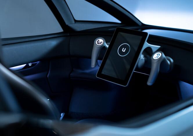 <strong>NYSKAPENDE:</strong> Stor skjerm på høykant, som Tesla - men her plassert midt i selve betjeningsmodulen som erstatter det tradisjonelle rattet. Foto: Uniti Sweden AB