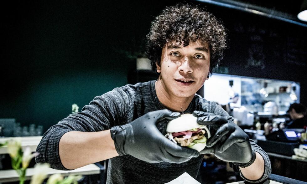 SPIS MED HENDENE: På ba-ga by Monsun skal du bruke hendene som spiseredskap, og om du synes det blir litt klissete kan du bruke hansker, slik kokken Jes Maglaque demonstrerer her. Foto: Christian Roth Christensen / Dagbladet