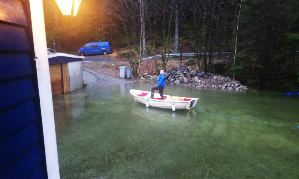 BÅT: Haavald Roald i Hausdalen var glad han flyttet bilene bort fra tunet i går. I dag var båt eneste mulige framkomstmiddel. Foto: privat / NTB scanpix