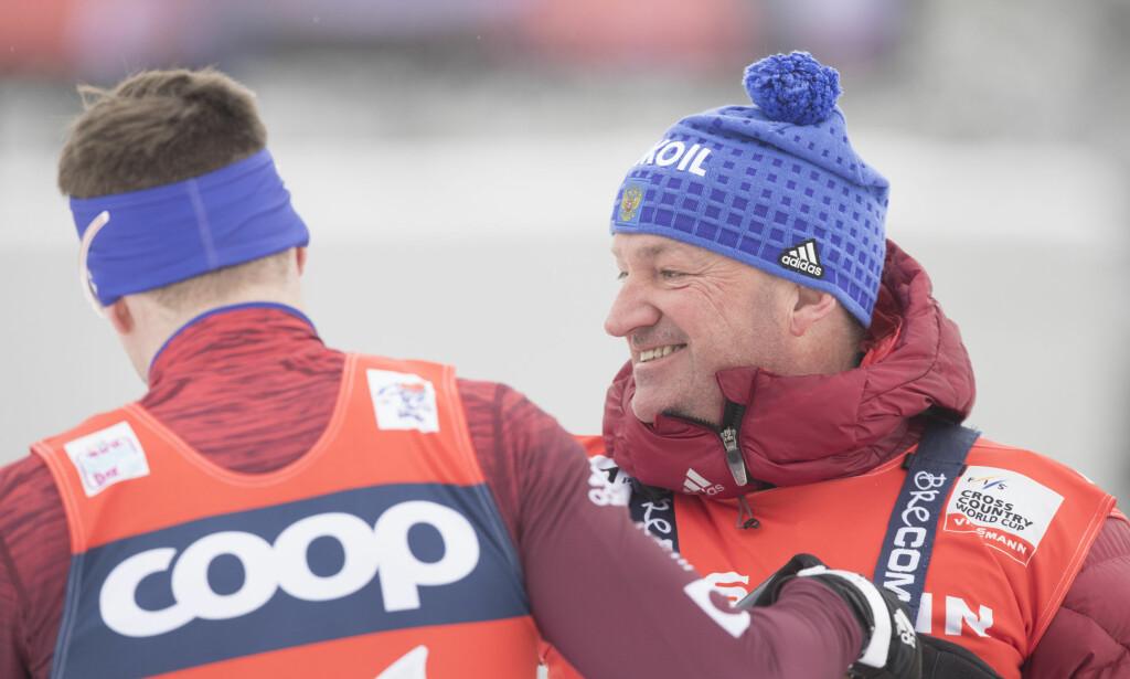 FRUSTRERTE: Sergej Ustjgov blir gratulert av sin tyske trener Markus Cramer etter dagens sprintseier i Lenzerheide, men begge er svært frustrerte over situasjonen de russiske utøverne står i. Foto: Terje Pedersen / NTB Scanpix