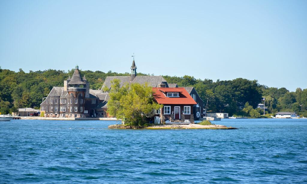 JUST ROOM ENOUGH-ØYA: Denne øya ved utløpet av Lawrence River i delstaten New York, er trolig verdens minste bebodde øy. I bakgrunnen inne på fastlandet ligger det langt mer prangende Boldt-slottet. Foto: Shutterstock / NTB Scanpix