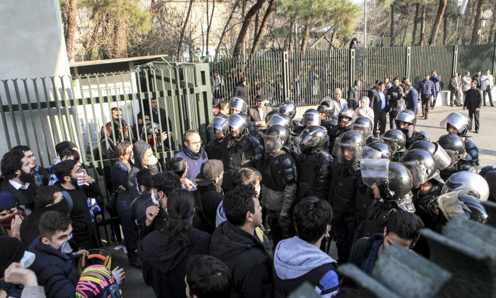 POLITI: Her forsøker iransk opprørspoliti å forhindre demonstrerende studenter fra å slå seg sammen med andre demonstranter i Teheran. Foto: AP Photo / NTB scanpix