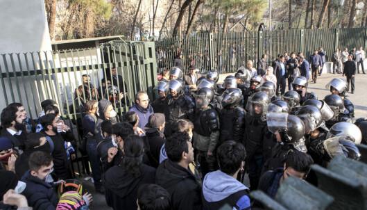 DEMONSTRASJON: Demonstranter og politiet overfor hverandre i Teheran. Foto: AP / NTB scanpix