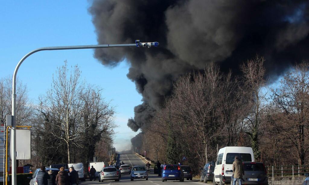 INFERNO: Svart røyk stiger opp fra en brennende tankbil på en motorvei nord i Italia tirsdag. Seks personer omkom i ulykken. Foto: Filippo Venezia / AP / NTB scanpix