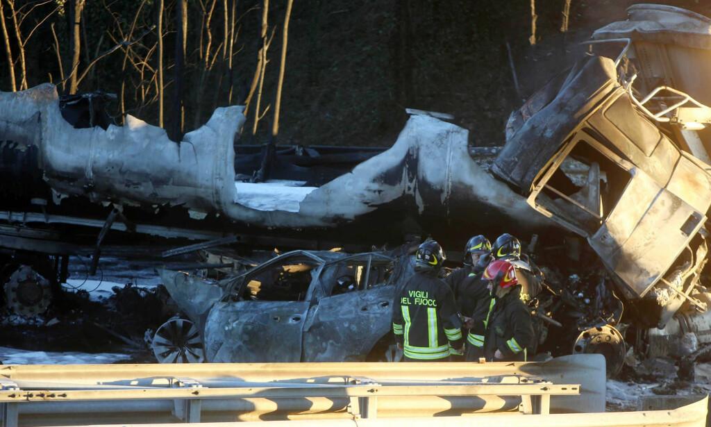 GRANSKES: Brannfolk gransker kjøretøyene som ble herjet av en voldsom brann etter en trafikkulykke på motorveien A21 i Italia tirsdag. Foto: Filippo Venezia / AP / NTB scanpix
