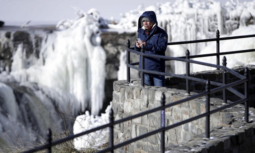SPRENGKULDE: Obdulio Arenas ser ut over de frosne vannmassene i Paterson Great Falls National Historical Park i delstaten New Jersey tirsdag. Store deler av USA har hatt en svært kald start på det nye året. Foto: Julio Cortez / AP / NTB scanpix