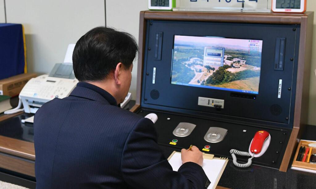 SNAKKER IGJEN: En sørkoreansk tjenestemann i grensebyen Panmunjom kommuniserer med en nordkoreansk tjenestemann under en telefonsamtale etter at direktelinjen ble gjenåpnet onsdag. Foto: Yonhap / AP / NTB scanpix