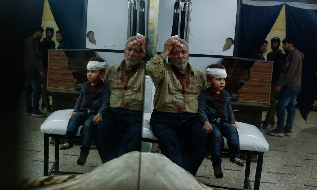 OVERLEVDE: En syrisk mann og et barn ble skadd etter flyangrepet mot byen Misraba i morges. Minst 23 sivile syrere skal være drept i flyangrepet, som enten det syriske regimet eller deres allierte, russerne, står bak. Foto: Hasan Mohamed / Afp / Scanpix