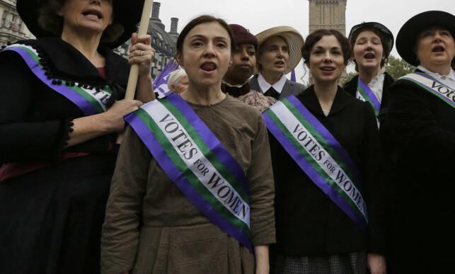 VELKJENTE FARGER: I 2012 valgte en britisk, feministisk organisasjon å kle seg ut som suffragettene, da også med de velkjente fargene som ble et symbol for stemmerett på 1900-tallet. Foto: NTB scanpix