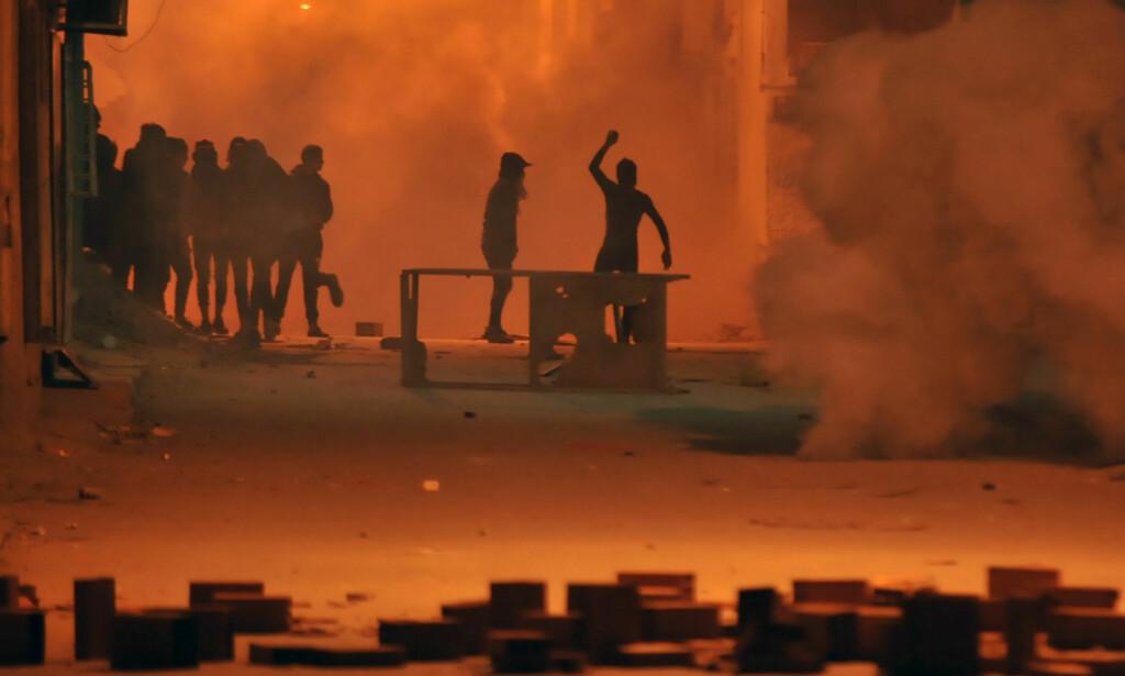 SAMMENSTØT: De siste døgnene har et stort antall tunisiere gått ut i gatene over hele landet. Demonstrantene er sinna over økende priser. En person er drept og over 300 arrestert. Bilder er fra Djebel Lahmer-området i hovedstaden Tunis i natt. Foto: Sofiene Hamdaoui / Afp / Scanpix