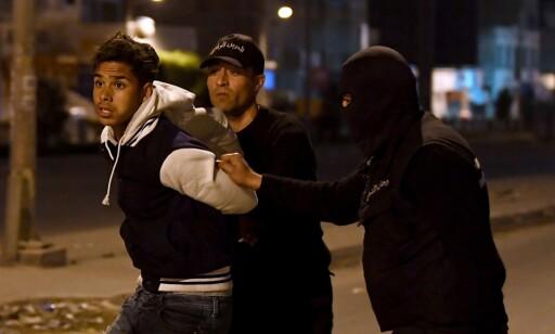 MASSEARRESTASJONER: En tunisisk demonstrant blir arrestert av sikkerhetsstyrker i utkanten av hovedstaden Tunis, natt til i dag. Mer enn 300 personer skal ha blitt arrestert det siste døgnet. Foto: Fethi Belaid / Afp / Scanpix