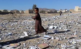 UTEN SKOLEGANG: En gutt har sikret seg en bok fra det som en gang var en skole i den nordlige byen Saada, men som ble bombet i helga. Foto: Naif Rahma / Reuters / Scanpix