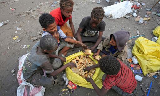 SPISER SØPPEL: En gjeng gutter spiser matrester som de har funnet på en søppeldynge i havnebyen Hodeida. Foto: Abduljabbar Zeyad / Reuters / Scanpix
