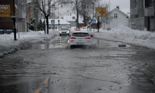 SMELTEVANN: Store mengder smeltevann dekker en gate i Skien tirsdag ettermiddag. Snøfallet har skapt store utfordringer for både trafikanter og offentlige etater i løpet av dagen. Foto: Lise Åserud / NTB scanpix
