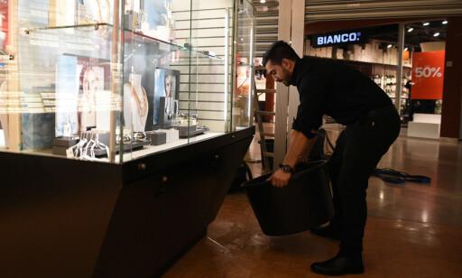 LEKKASJE: Butikksjef Bakwan Hassan gjorde sitt beste for å fange opp noe av vannet som rant gjennom taket. Foto: Endre Vellenes / Dagbladet