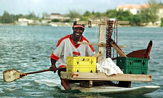 SALG AV VARER PÅ STRANDA: Antonio Lawrence, 42, pader på et surfebrett med varer som han selger til turister i Montego Bay. Foto: Scanpix