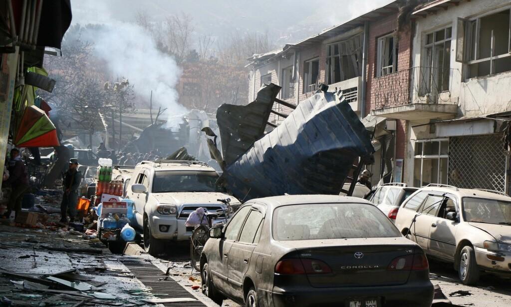 KAOS, DØD OG SKADER: Bilbomben, som var plassert i en ambulanse (røyk i bakgrunnen), gikk av lørdag innenfor den strengeste sikkerhetssonen i Kabul, her i Sidarat Square. Søndag var det offisielle tallet på døde minst 103 og antallet skadde 235. Foto: Haroon Sabawoon, Anadolu Agency / NTB Scanpix