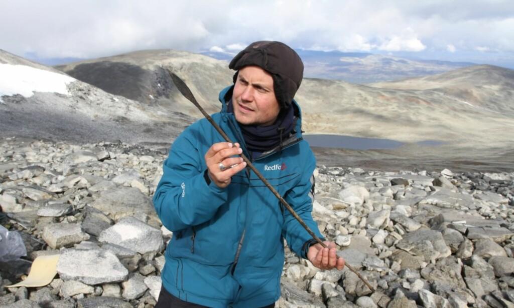 EN AV 200: Arkeolog Elling Utvik Wammer med en 1500 år gammel pil. Sammen med arkeologkolleger har han funnet nesten 200 piler og snart 2000 arkeologiske gjenstander i snøen i Oppland de siste ti årene. FOTO: Secrets of the Ice / Oppland Fylkeskommune