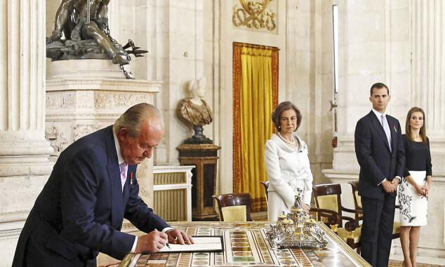 TUNGT HJERTE: Juan Carlos signerer dokumentet der han frasier seg tronen og abdiserer. Kona Sofia, Felipe og Letizia følger med i bakgrunnen. Foto: AP/ NTB scanpix