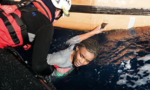 HOLDER SEG FAST: Kvinnens faste grep rundt håndtaket på gummibåten kan ha reddet livet hennes. Kvinnen, hennes barn og et titalls andre personer ble fraktet med helikopter til Tunisia for medisinsk behandling. Foto: Laurin Schmid