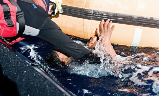 KJEMPER FOR LIVET: Her får kvinnen hjelp med å få hodet over vann. Foto: Laurin Schmid
