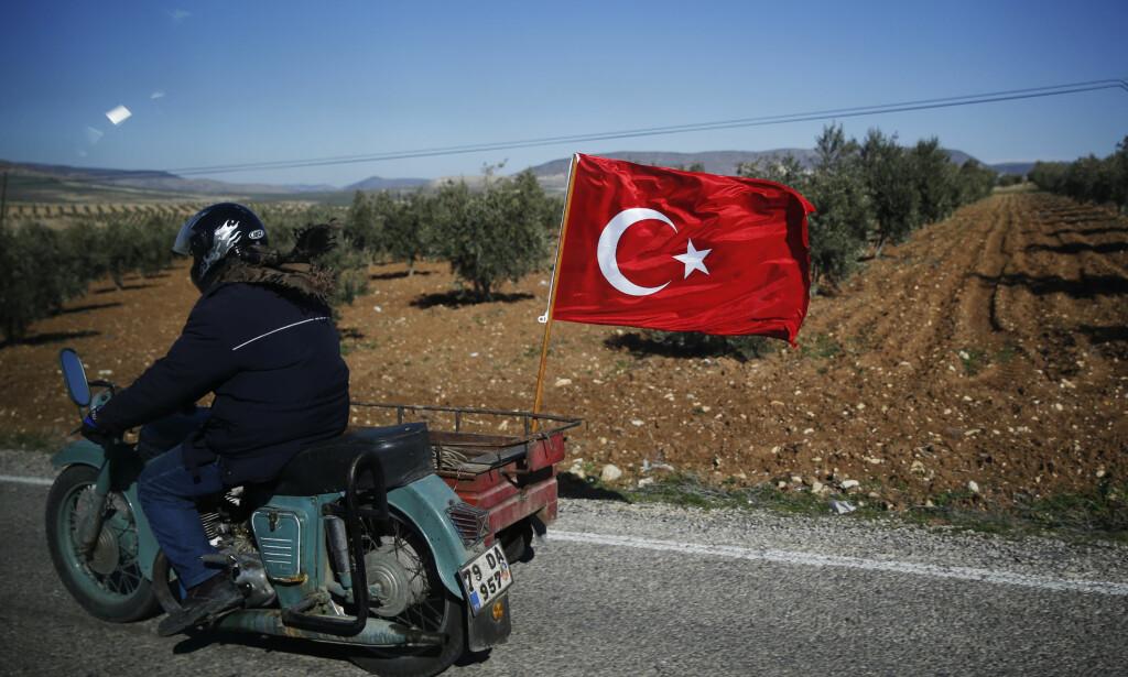 HEIER FRA SIDELINJEN: En tyrker ved grensen til Syria viser sin støtte til tyrkiske soldater som kjemper mot kurdere nord i Syria. Tyrkiske myndigheter slår hardt ned på kritikk av militæroffensiven, noe som nå har rammet hele styret i den tyrkiske legeforeningen. Foto: Lefteris Pitarakis / AP / NTB Scanpix