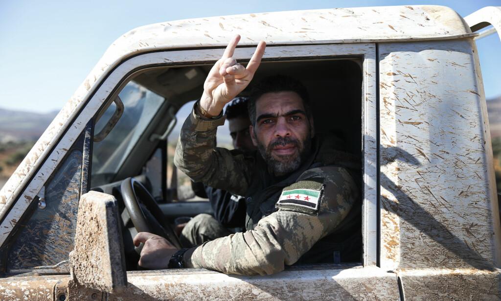 PÅ VEI MOT GRENSEN: Soldater fra Den frie syriske her, som har som mål å styrte regimet i Syria, blir kjørt til mot den syriske grensen. Foto: Lefteris Pitarakis/ AP/ NTB Scanpix