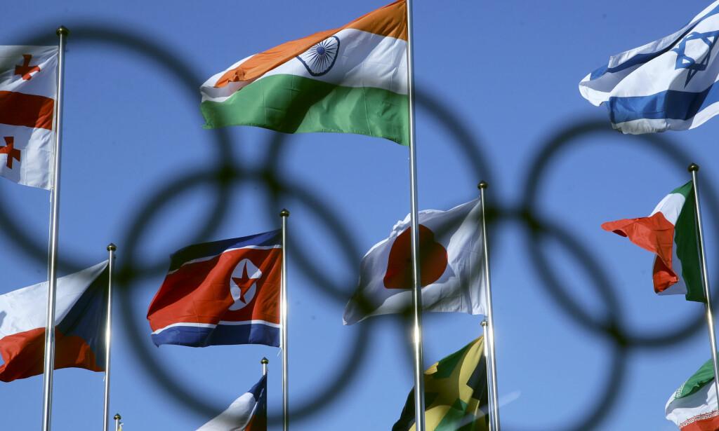 SAMLENDE: «Vi er ett (folk)» var en av velkomstplakatene de Nord-Koreanske idrettsutøverne ble møtt med. Charlie Riedel/ AP/ NTB Scanpix