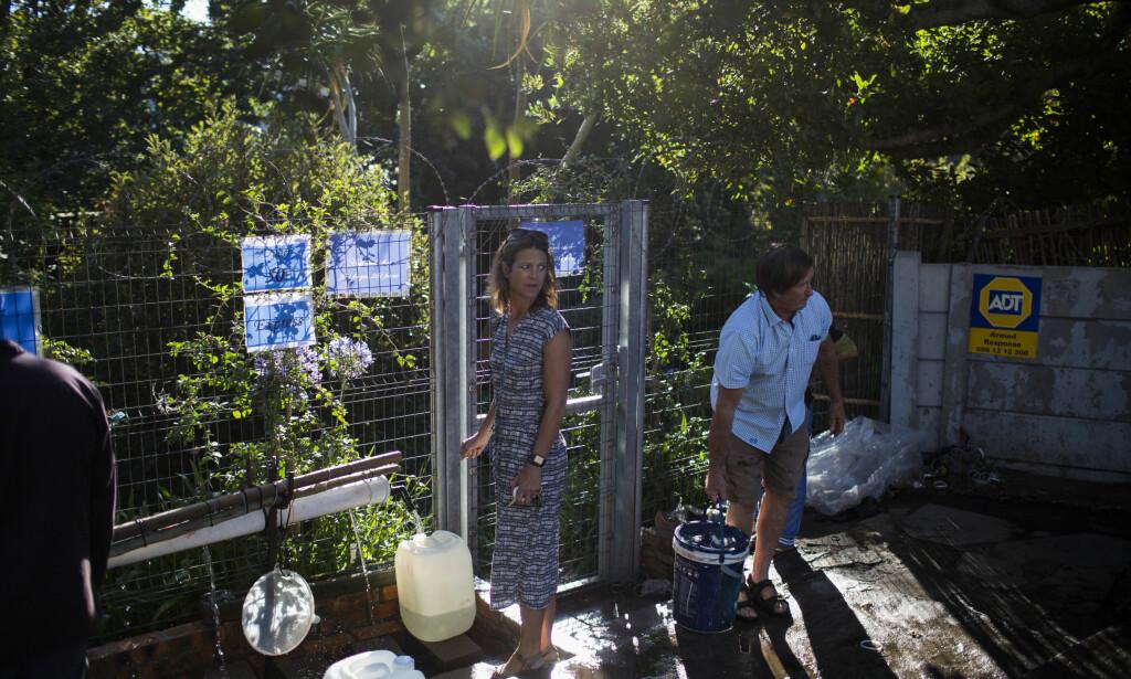 HAMSTRER VANN: Her henter innbyggere i Cape Town vann ved en naturlig kilde i byen. Dersom det ikke snart kommer regn, vil de fra 12. april bare kunne bruke 25 liter vann i døgnet. Foto: AP Photo / Bram Janssen / NTB Scanpix