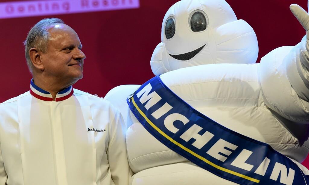 LEGENDE: Joel Robuchon med tre stjerner i Michelinguiden poserer sammen med Michelinmaskoten under utdelingen av nye michelinstjerner i Singapore i fjor. Noen kokker drømmer hele livet om en stjerne i matbibelen. Andre drømmer om å kvitte seg med stjernen, og starte et nytt liv. Det gis det rom for nå. Foto: AFP Roslan Rahman