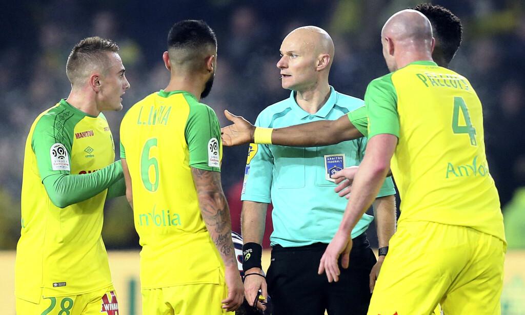 SPARK: Tony Chapron omgis av Nantes-spillere etter at han sparket forsvareren Diego Carlos i sinne over en kollisjon som viste seg å være et rent uhell. Nå er dommeren utestengt i tre måneder. Foto: David Vincent, AP / NTB scanpix