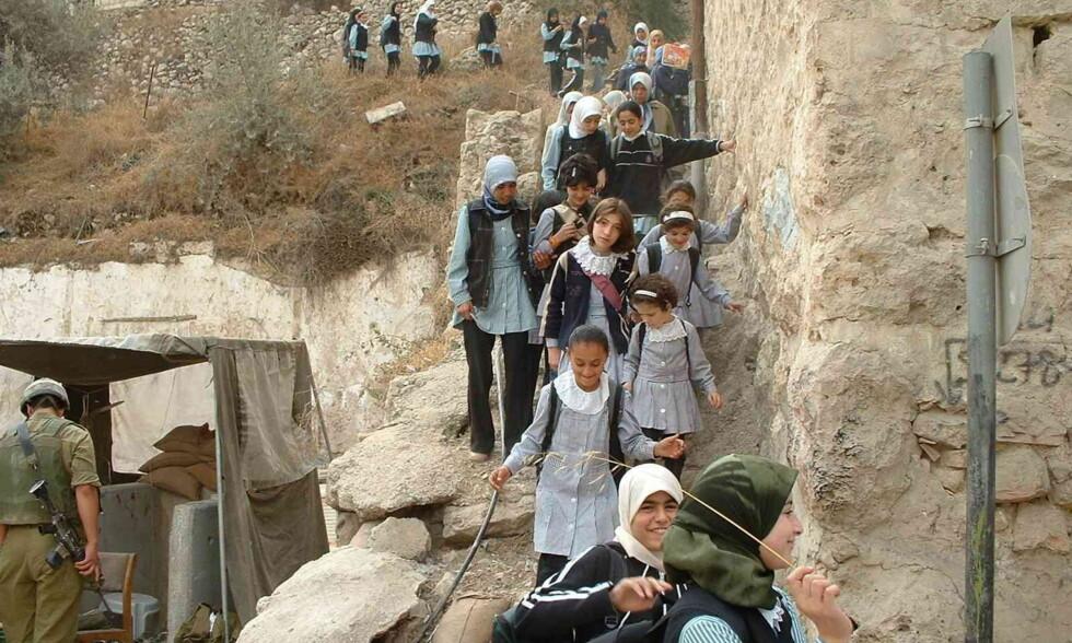 FÅR FØLGE: De palestinske barna som går på Cordoba-skolen i Hebron trenger daglig å bli fulgt av internasjonale observatører for å unngå trakassering, enten fra israelsk militære i sjekkposter, eller fra israelske bosettere. De siste to åra har Israel nektet stadig flere ledsagere innreise til Israel - og dermed de palestinske områdene. Foto: Kirkens Nødhjelp