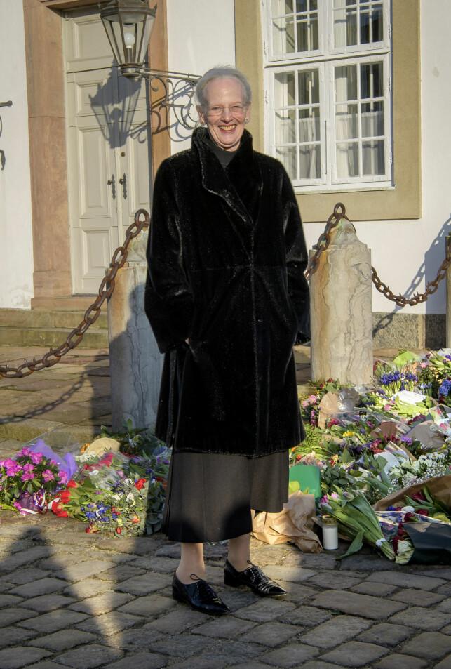 BLOMSTERHAV: Dronning Margrethe tok seg god tid til å se på kondolansebukettene, men virket ikke preget. Foto: Martin Høien / Billedbladet