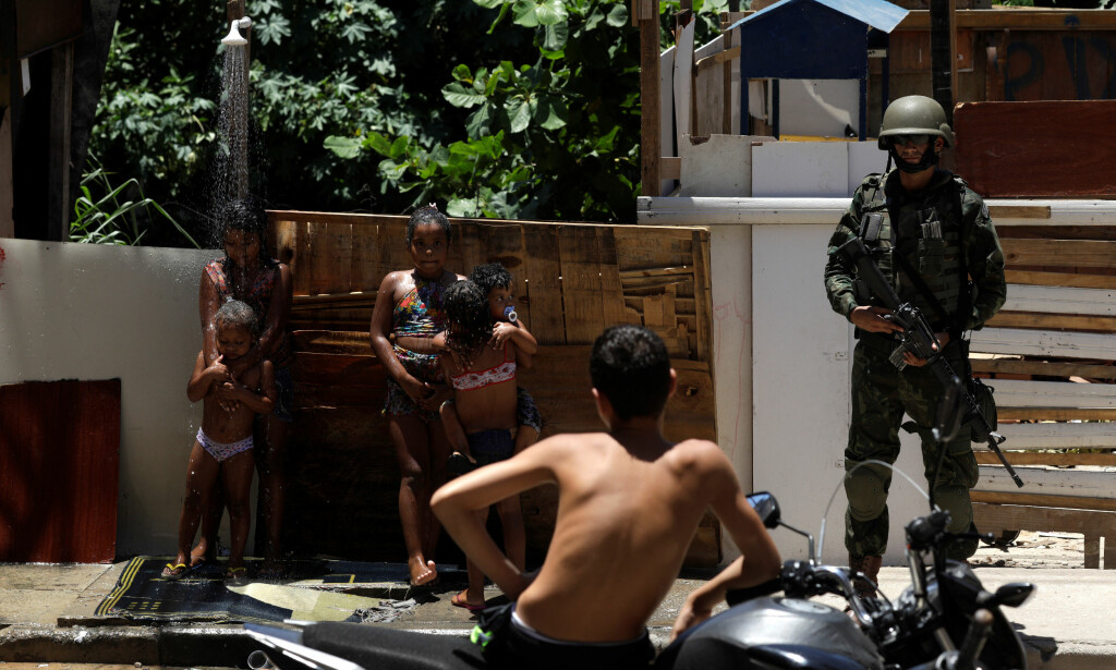 MILITÆRE: Barn leker i en dusj i en bakgate i Manguinhos-slummen i Rio de Janeiro. Foto: Reuters /Scanpix