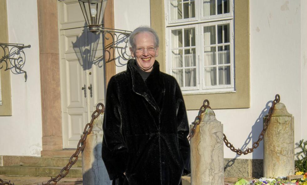 SMILER ETTER SORGEN: Dronning Margrethe av Danmark mistet ektemannen sin tirsdag kveld. Da hun onsdag viste seg og kikket på blomsterhavet, var det derimot ingen sorg å skimte hos dronningen. Nå tror sognepresten at hun har svaret på hvorfor. Foto: Martin Høien/Billedbladet