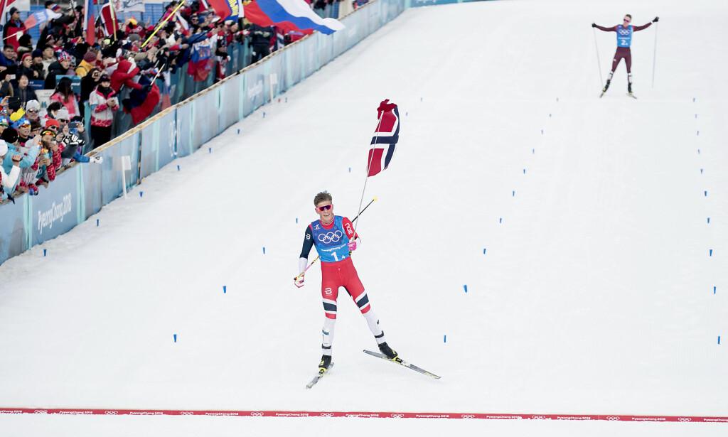 GULL: Johannes Høsflot Klæbo kunne ta seg tid til å få med seg et flagg på oppløpet etter å ha avgjort tidlig mot russiske Denis Spitsov. Foto: Bjørn Langsem/Dagbladet