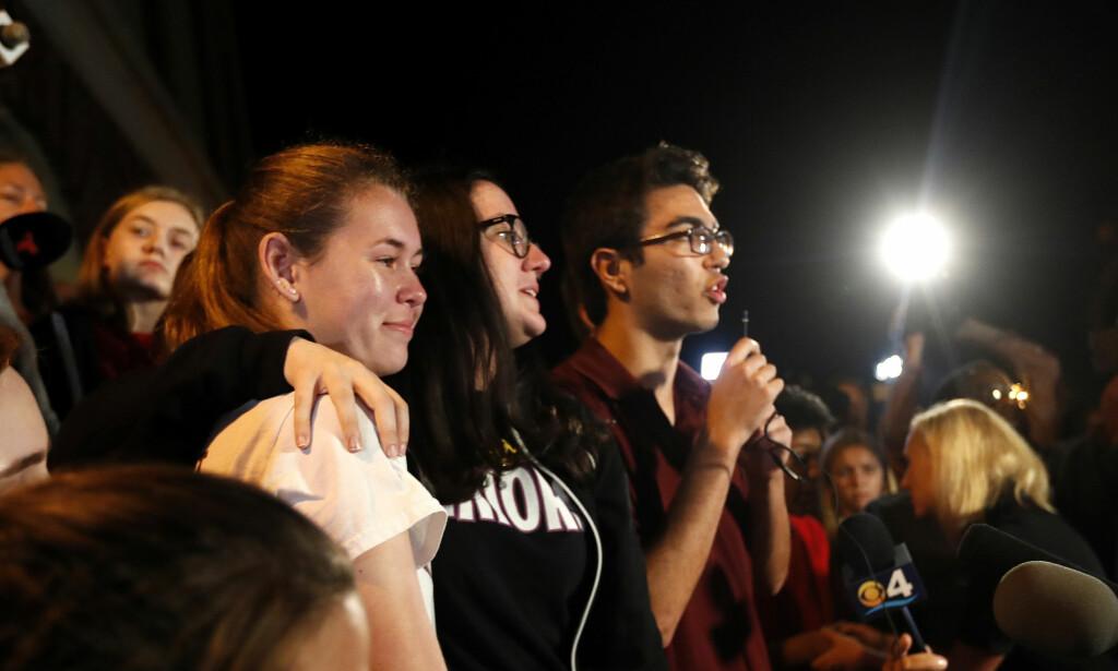 VIL HA STRENGERE LOVER: Diego Pfeiffer, en elev fra skolen i Florida hvor 17 mennesker ble drept i forrige uke, snakker til støttespillere og pressefolk på en annen videregående skole i delstaten denne uken. Medelevene Sophie Whitney (t.v.) og Sarah Chadwick står sammen med Pfeiffer. Foto: AP/NTB scanpix